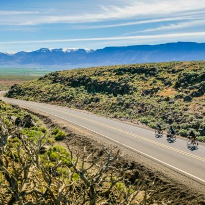 image of cyclists riding the oregon outback scenic bikeway with mountains in the background
