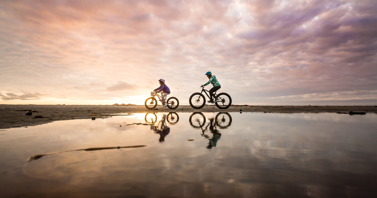 2 people riding their bikes on the coast