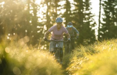 Two women mountain biking on a grassy, sunny biking trail.