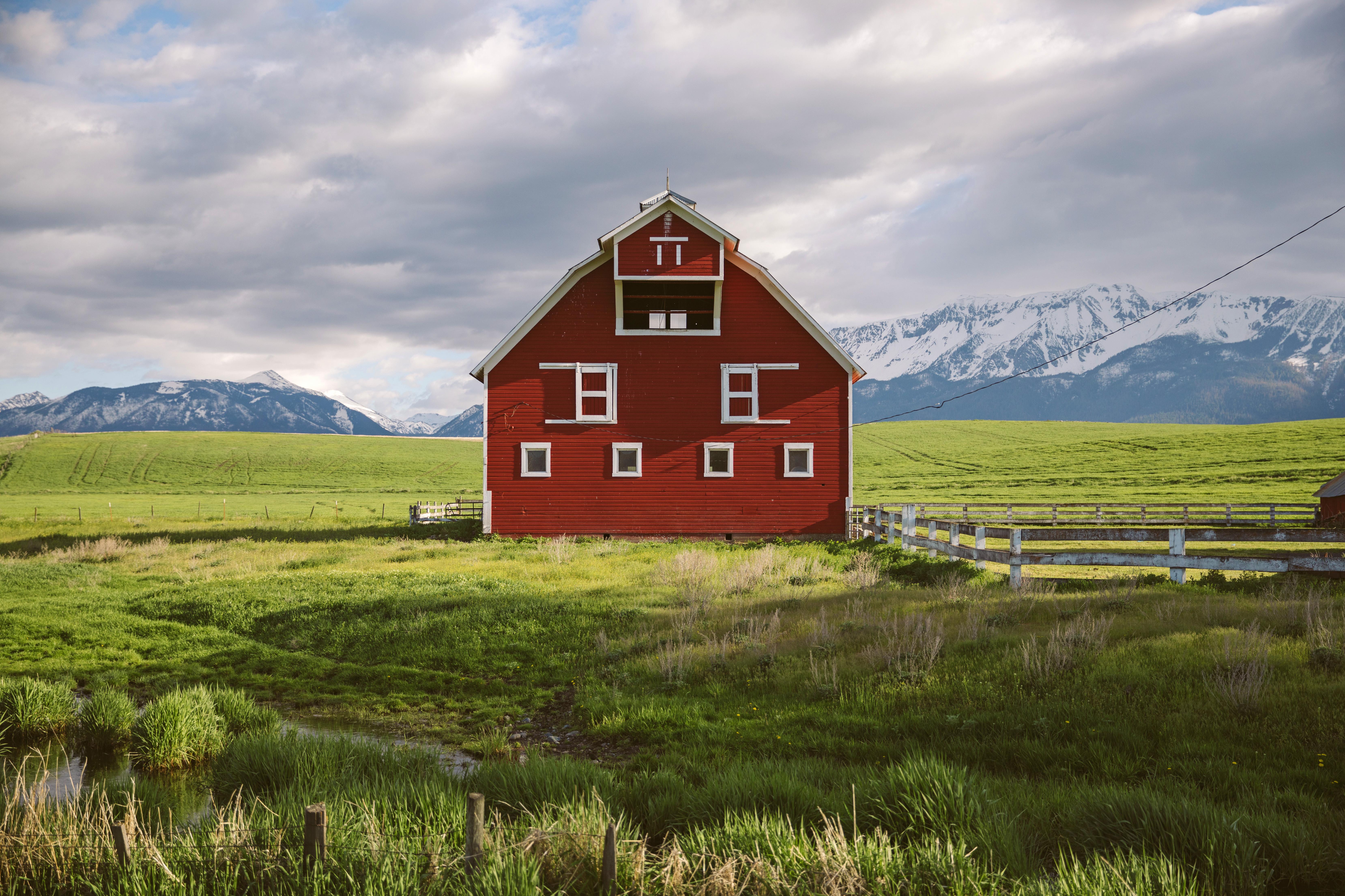 Red barn sitting center in beautiful green landscape in the Wallowas inEastern Oregon.