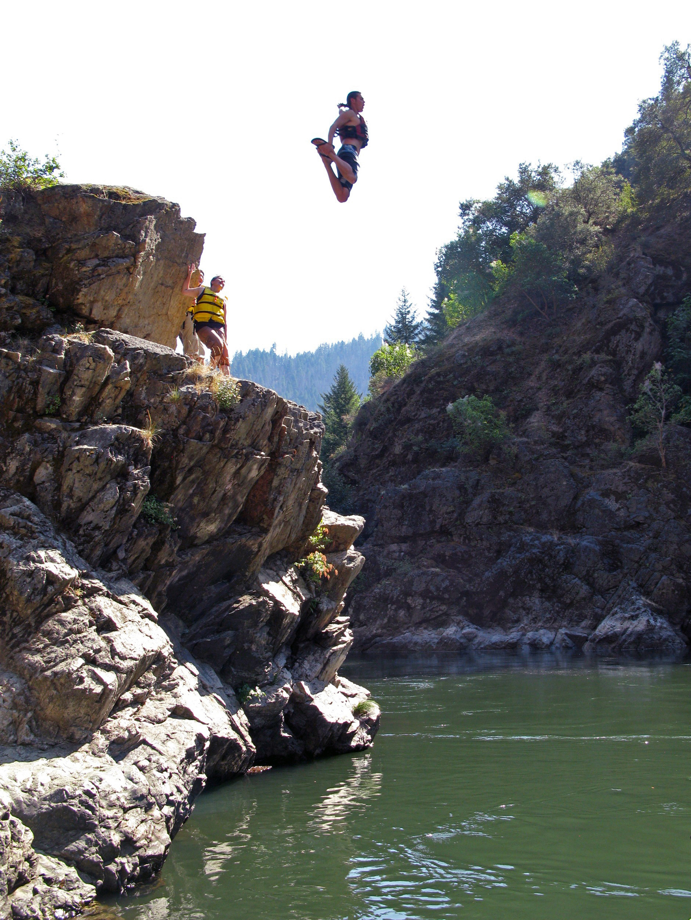Woman jumping off rock into a river