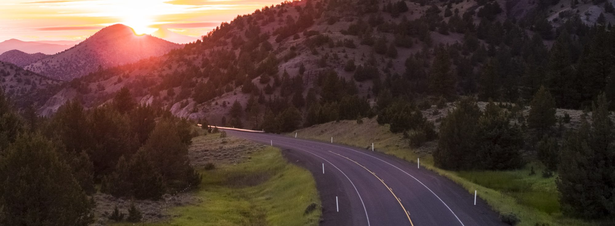 Road in Eastern Oregon with sunset in the distance.