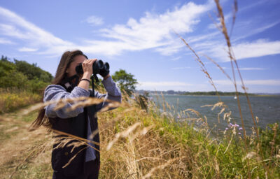 Woman looking out at the coast with binoculars, surrounded by beach grass.