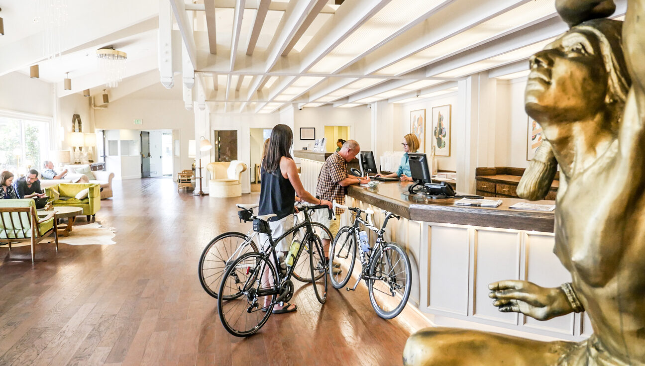 Hotel lobby, guests at front desk with bicycles.