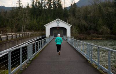 Woman running across white covered bridge.