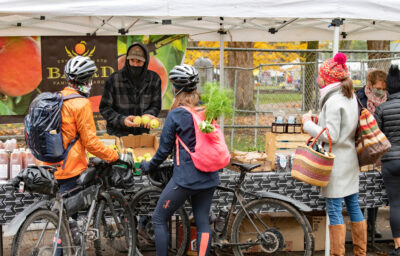 Image of cyclists shopping for produce at the Portland Farmers Market.
