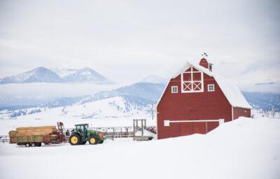 Red barn, tractor pulling hay in snowy Eastern Oregon.