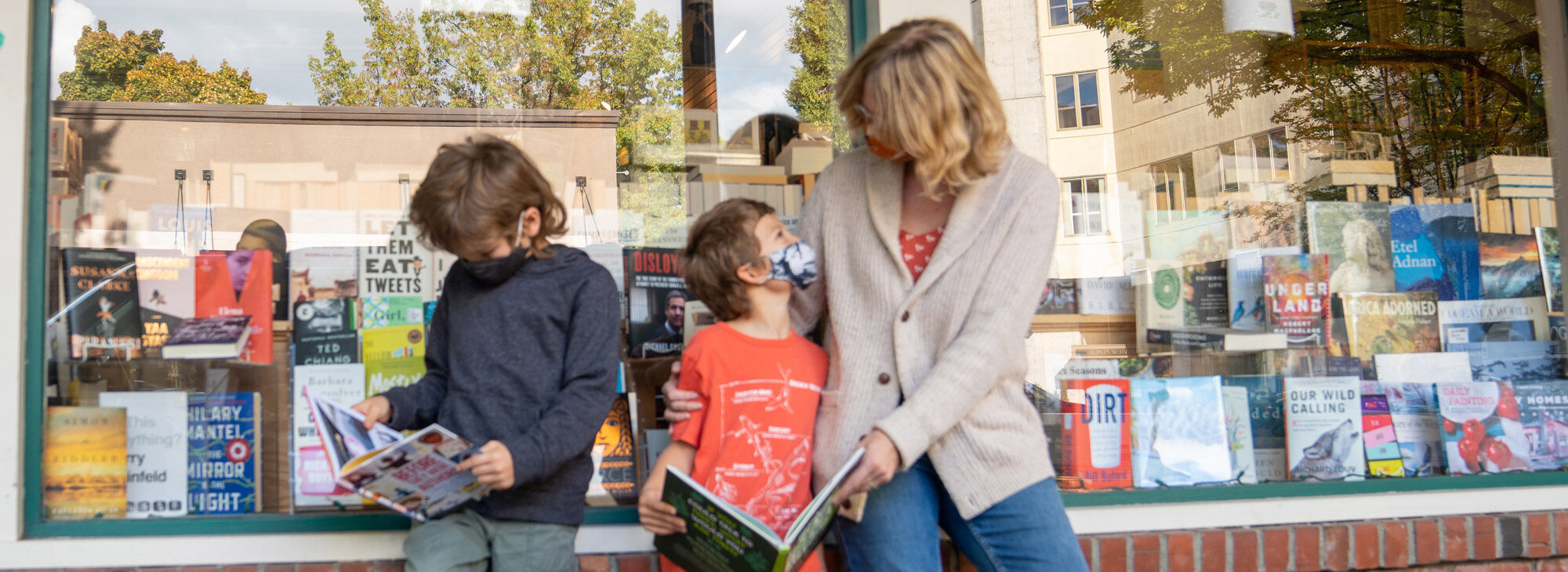 Parent and two children enjoying books outside bookstore.