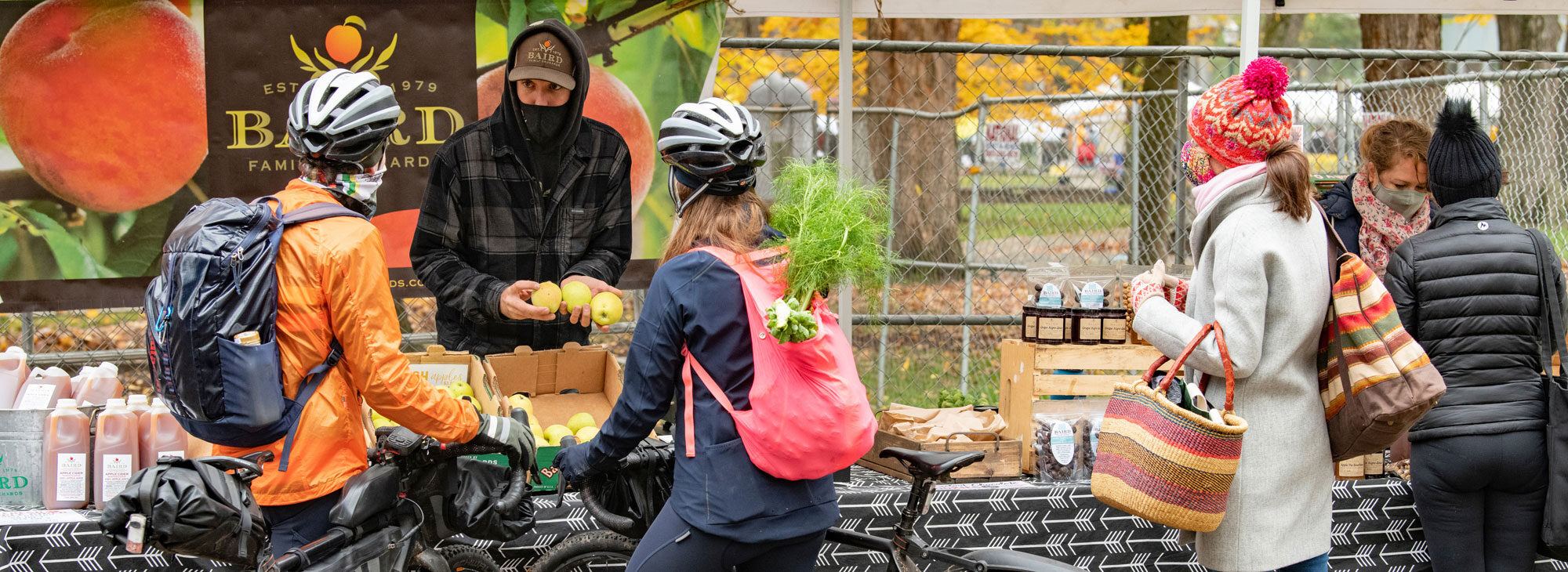 Cyclists shopping for produce at the Portland Farmers Market.