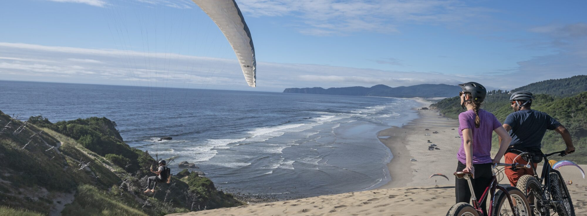 Two cyclists riding through the sand with a view of a hang glider and the ocean in Pacific City.