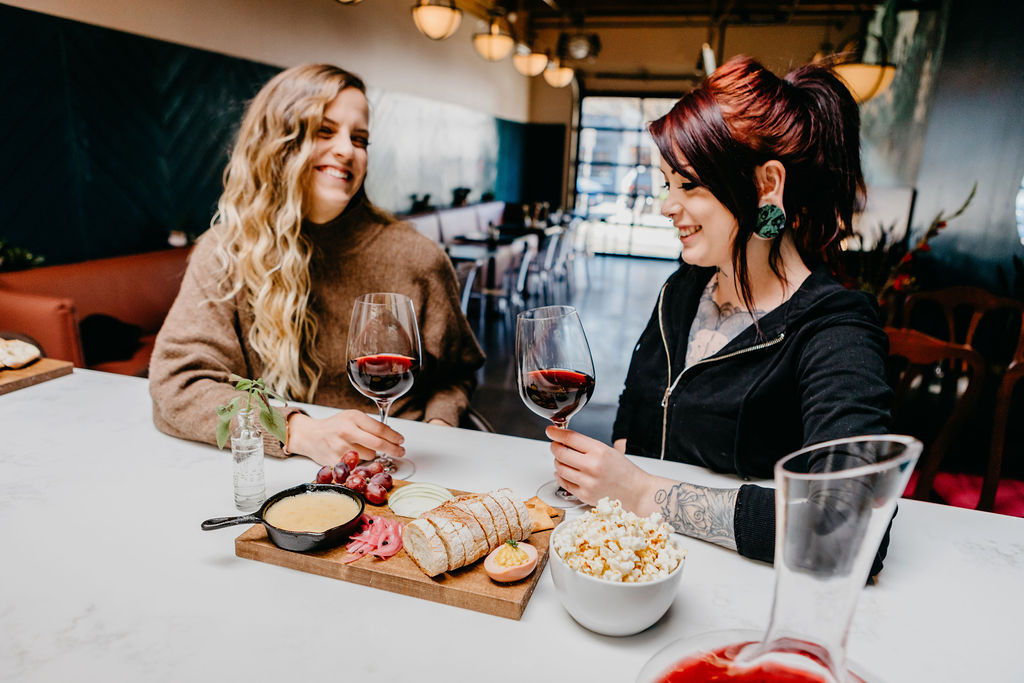 Two women enjoying wine and appetizers at Stem Wine Bar in Portland.