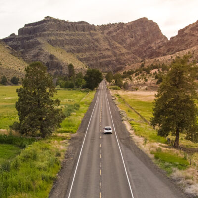Electric vehicle driving down byway in Eastern Oregon.